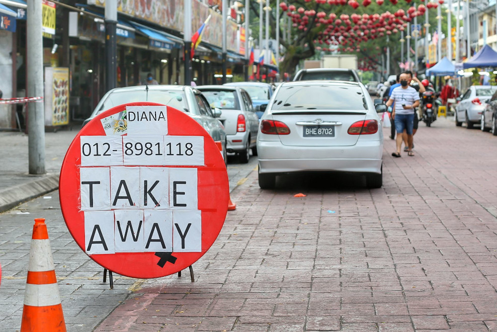 A takeaway signboard is seen in Jalan Alor. People are not allowed to dine in at the restaurant during the movement control order June 2, 2021. — Picture by Ahmad Zamzahuri