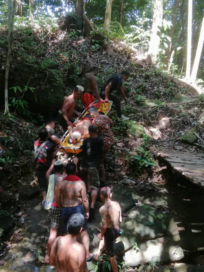 Fire and Rescue Department personnel and villagers carrying the victim to a waiting ambulance. — Borneo Post pic