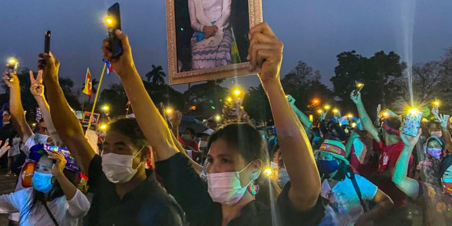 A Myanmar migrant living in Thailand holds a portrait of detained civilian leader Aung San Suu Kyi while she and other hold up their mobile phone lights during a night protest in Chiang Mai on April 4, 2021. ― ETX Studio pic