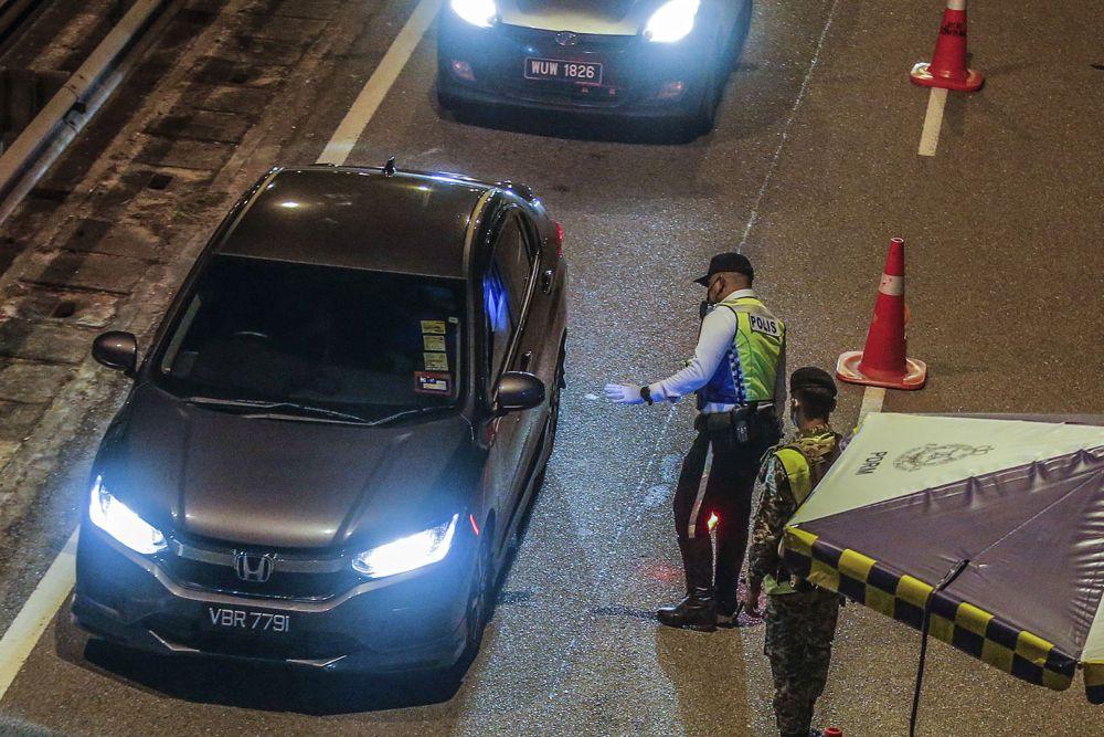 Police and Armed Forces personnel conduct checks on vehicles at a roadblock at Jalan Ipoh-Rawang June 1, 2021. — Picture by Hari Anggara