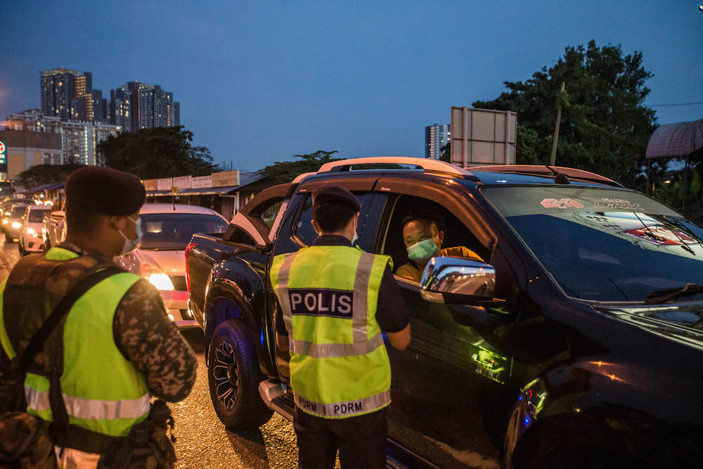 Police and Armed Forces personnel conduct checks on vehicles at a roadblock on Jalan Ipoh-Rawang June 6, 2021. — Picture by Firdaus Latif