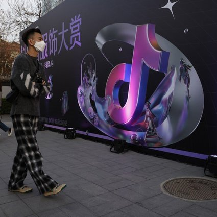 A woman speaks on her phone near the logo for Douyin, the Chinese version of TikTok, in Beijing on March 31. After Tencent's vice-president compared personalised short videos to pig feed, ByteDance fired back on Friday, calling the comments stigmatising. Photo: AP