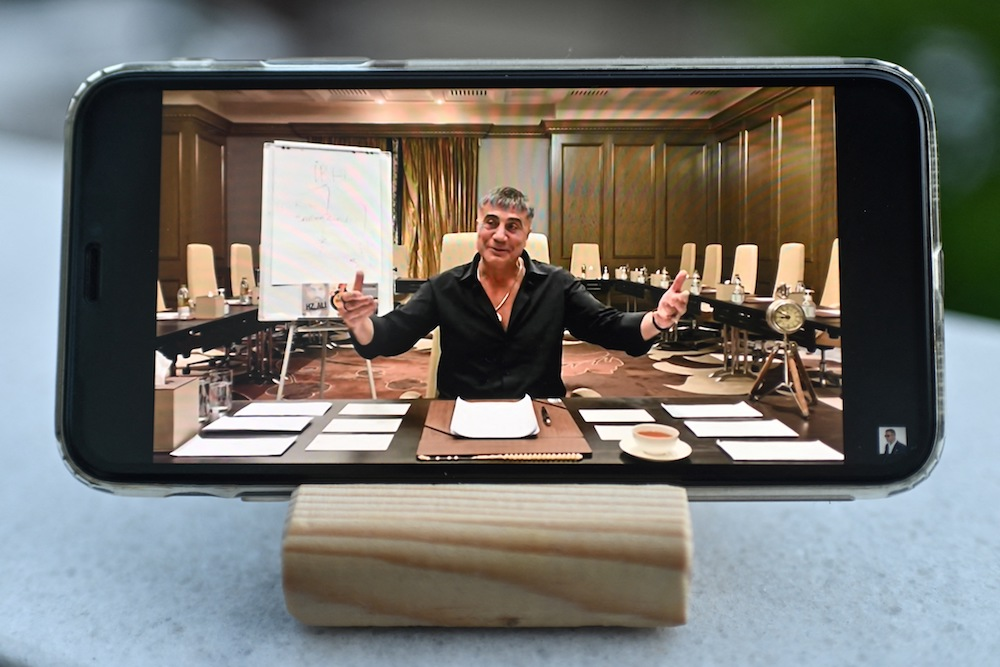 A photograph taken on May 26, 2021 in Istanbul shows Sedat Peker speaking on his YouTube channel on a mobile phone. (AFP)