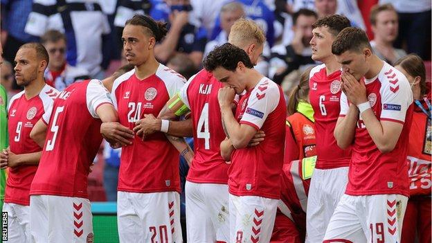 The Danish players protect Christian Eriksen
