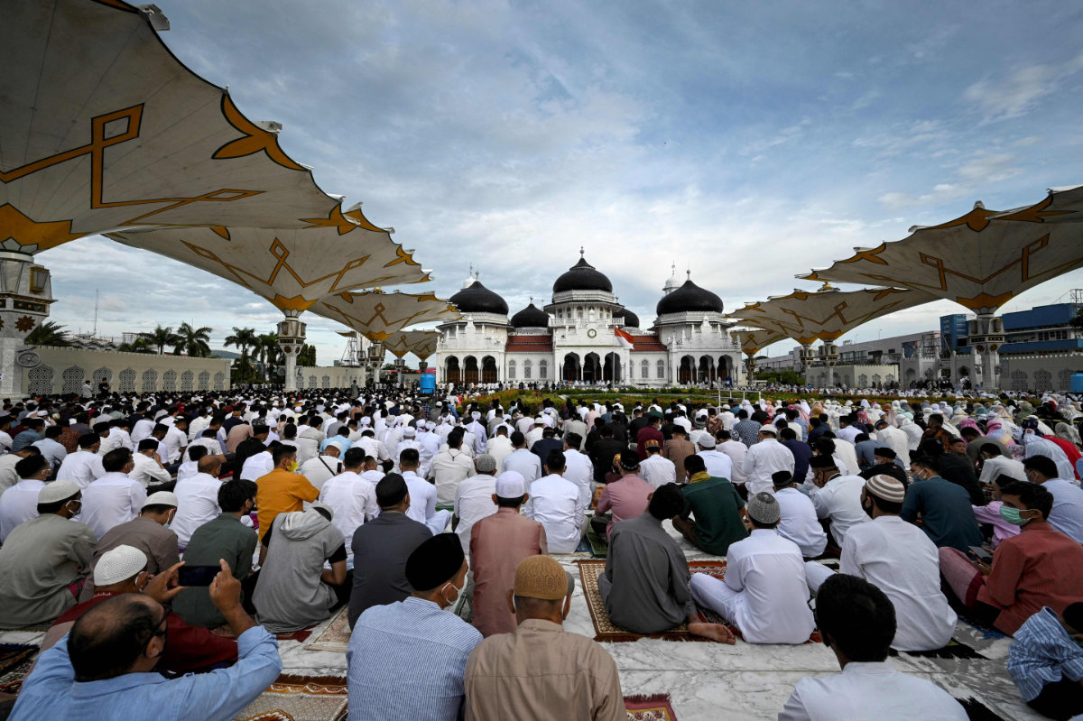 Worshippers appear to dispense with social distancing measures as they attend prayers at the Baiturrahman Grand Mosque in Banda Aceh, Indonesia, on July 20, 2021. (AFP)