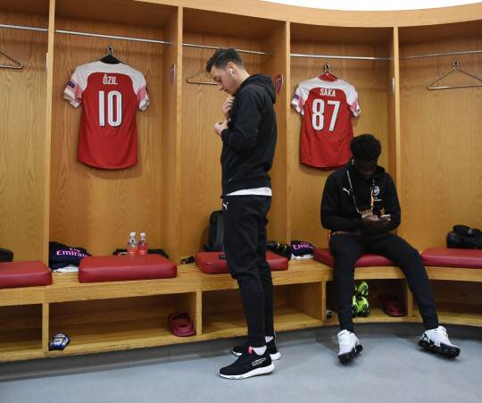 Mesut Ozil and Bukayo Saka look on in Arsenal dressing room