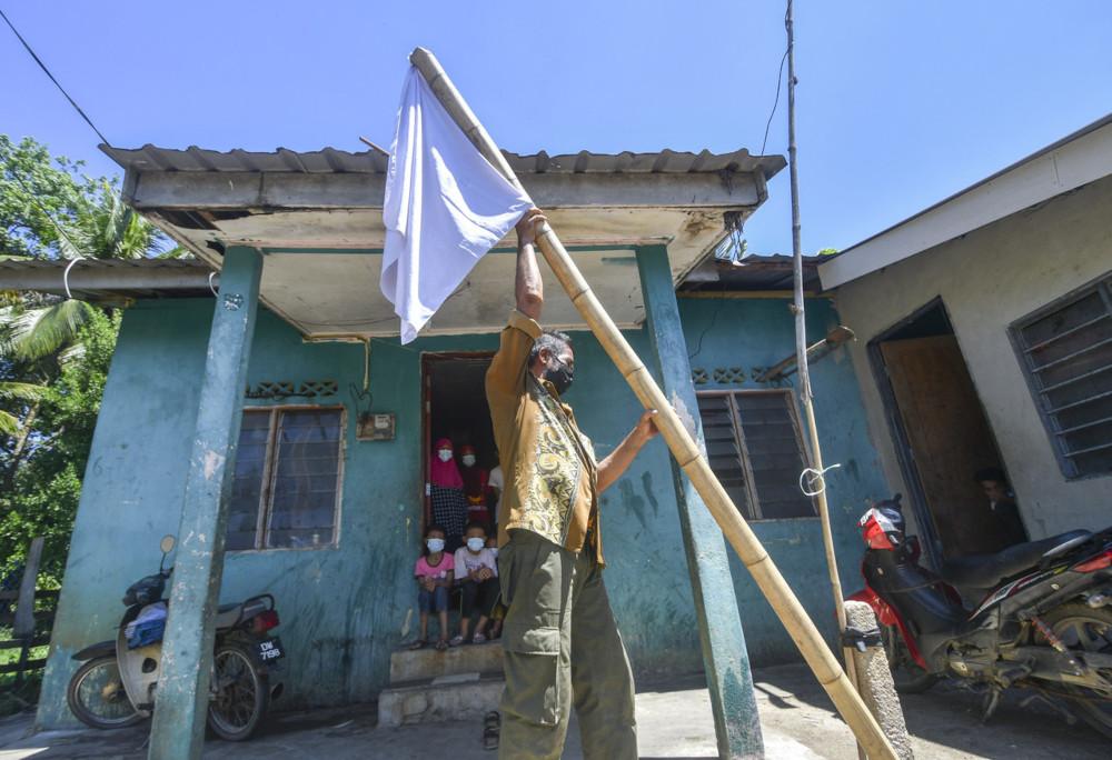Zaidi Dollah, 56, hoisting a white flag in front of his house in Kampung Banggol, Gelang Mas, Kelantan, July 1, 2021. — Bernama pic