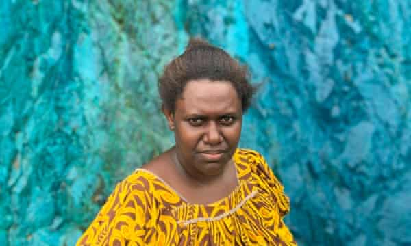 Theonila Roka Matbob, the member for Ioro, standing in the pit of the Panguna mine where polluted water has discoloured the land and river beds.