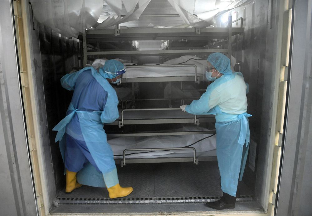 Hospital Sultanah Aminah staff are pictured in a container which doubles as a morgue as they handle remains of deceased Covid-19 patients in Johor Baru July 21, 2021. — Bernama pic