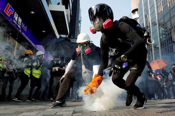 An anti-government protester holds a tear gas canister during a protest in Hong Kong, during October 2019