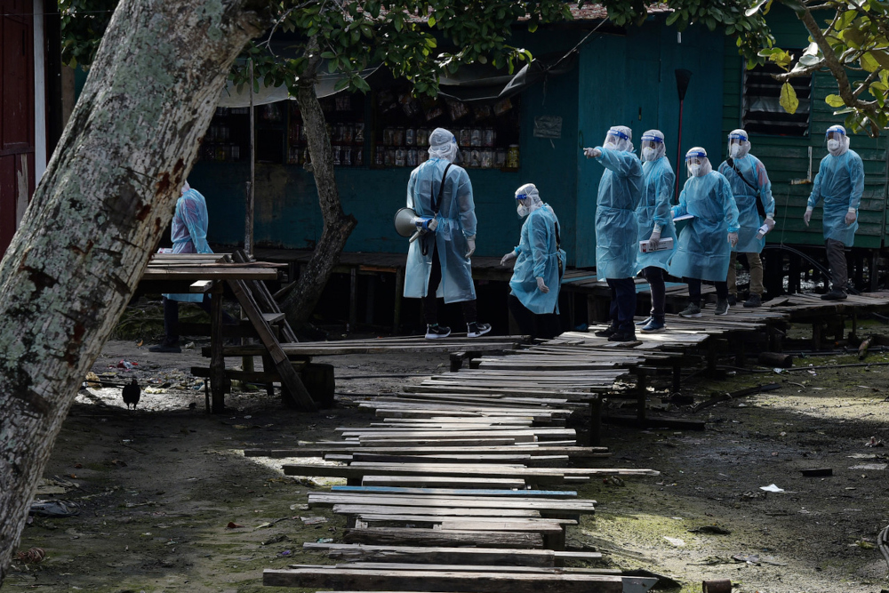 Health workers with police and Labuan Disaster Management Committee members garbed in PPEs while conducting house-to-house active case detection at the squatters' settlement in Kampung Saguking recently, July 18, 2021. — Bernama pic