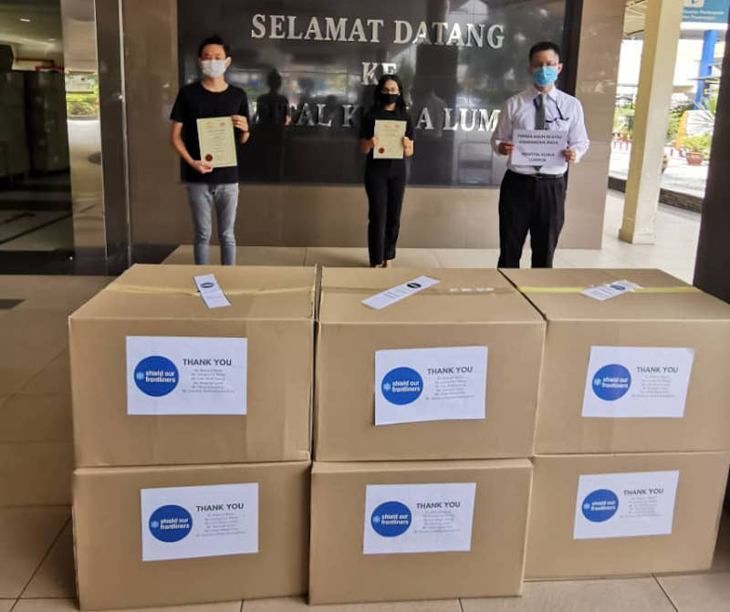 Au Jun Wei (left) and Leong Himn Yau (centre) handing over free face shields to a representative from Hospital Kuala Lumpur last year. Together with Karishma Menon, they are the founders of Feed Selangor.