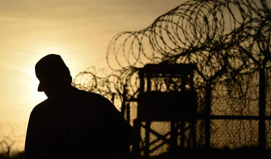"""An US soldier walking next to the razor wire-topped fence at the abandoned """"Camp X-Ray"""" detention facility at the US Naval Station in Guantanamo Bay, Cuba, April 9, 2014. (AFP)"""