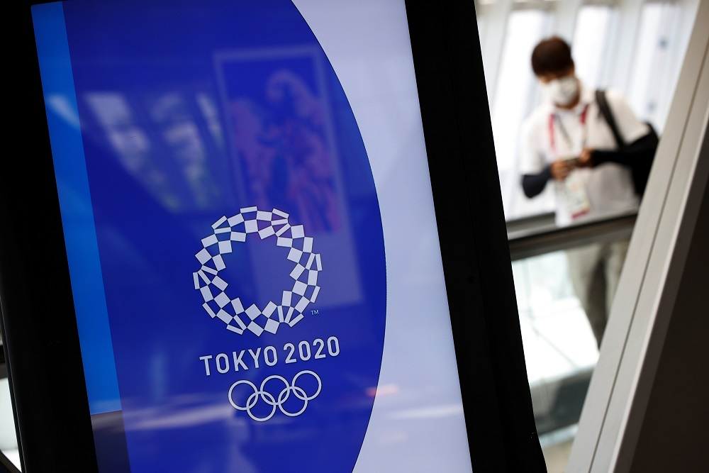 A man wearing a face mask walks past Tokyo 2020 Olympic Games signage at the Main Press Centre in Tokyo, Japan July 17, 2021. ― Reuters pic