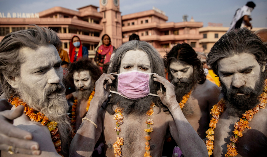 """A Hindu man wears a mask before the procession for taking a dip in the Ganges river during Shahi Snan at """"Kumbh Mela"""" amidst the spread of the coronavirus disease (COVID-19), in Haridwar, India, April 12, 2021. (REUTERS)"""