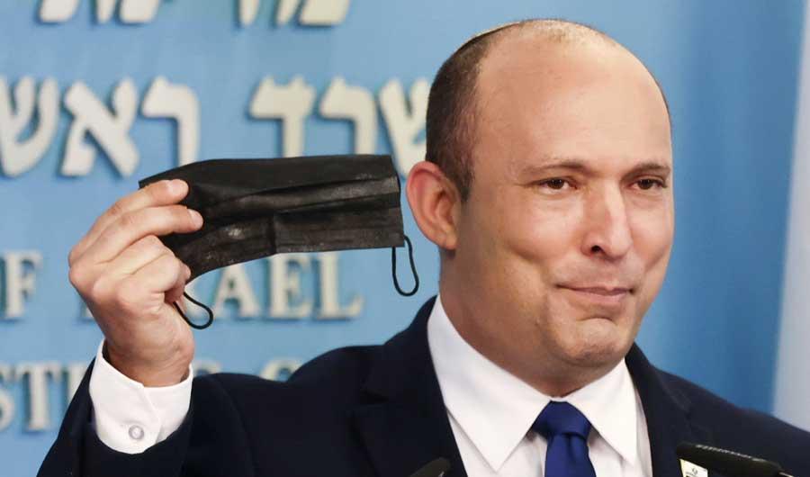 Israeli Prime Minister Naftali Bennett holds a face mask during a news conference in Jerusalem, July 14, 2021. (REUTERS)