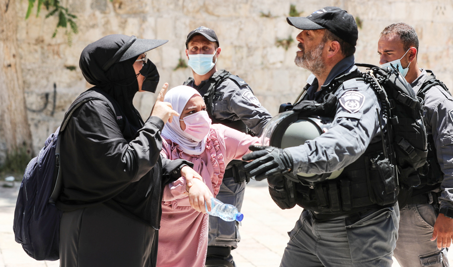 Palestinian women argue with an Israeli security force member after brief clashes erupted between Israeli police and Palestinians at al-Aqsa Mosque in Jerusalem's Old City, July 18, 2021. (REUTERS)