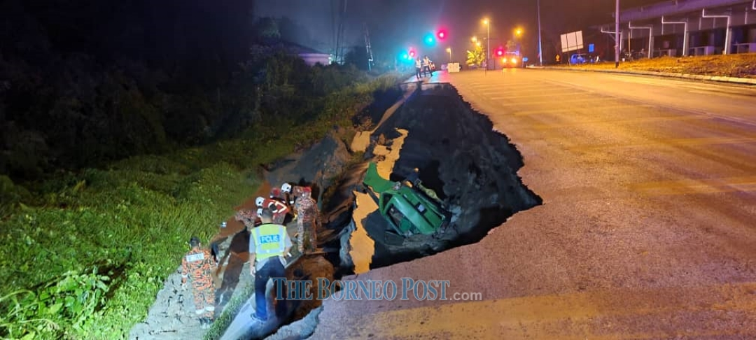 Fire and Rescue personnel at the scene of the accident where the road has caved in near Bau. ― Picture courtesy of Fire and Rescue Department (Bomba)