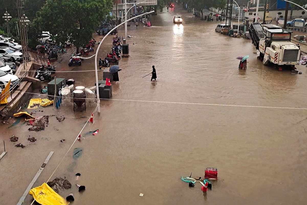 People wade through flood waters along a street following heavy rains in Zhengzhou in China's central Henan province on July 20, 2021. (AFP)