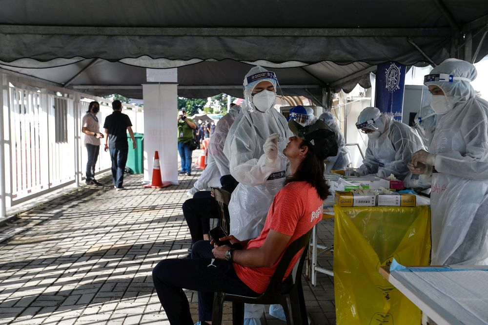 Healthcare workers collect swab samples to test for Covid-19 at the City Stadium in George Town July 5, 2021. — Picture by Sayuti Zainudin