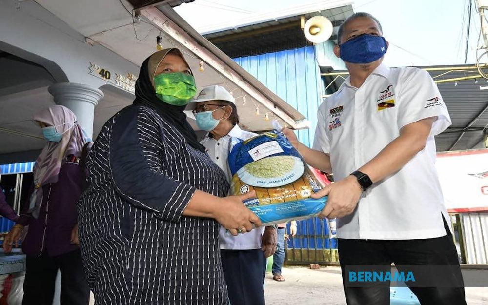 File picture of Datuk Seri Fadillah Yusof handing out food aid to a resident of Kampung Sungai Bedil Besar July 10, 2021. — Picture via Twitter/Bernama