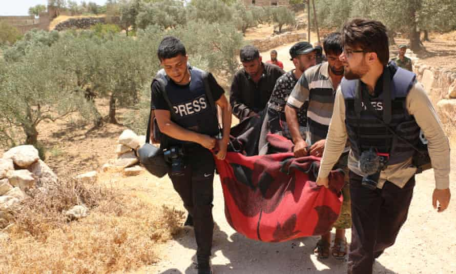 Members of the press carry a body of a victim pulled from the wreckage of a house after shelling by the forces of the Bashar al-Assad regime and its allies in Idlib province on 17 July.
