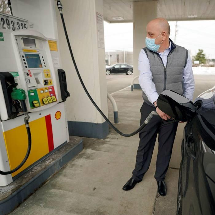 A man wearing mask pumps gasoline at a Shell gas station