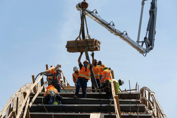A Skanska AB construction worker guides a crane carrying lumber as a concrete boom pours concrete on the Sixth Street Viaduct replacement project in Los Angeles, California