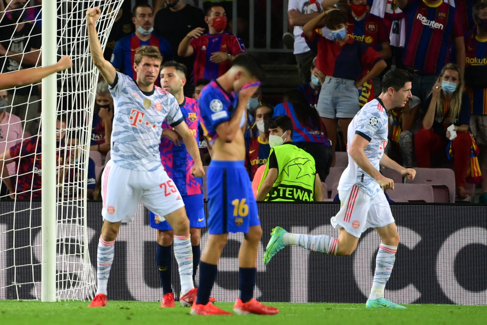 Bayern Munich forward Robert Lewandowski celebrates his goal with Thomas Mueller during the Uefa Champions League first round group E football match between Barcelona and Bayern Munich at the Camp Nou stadium in Barcelona, September 14, 2021. — AFP pic