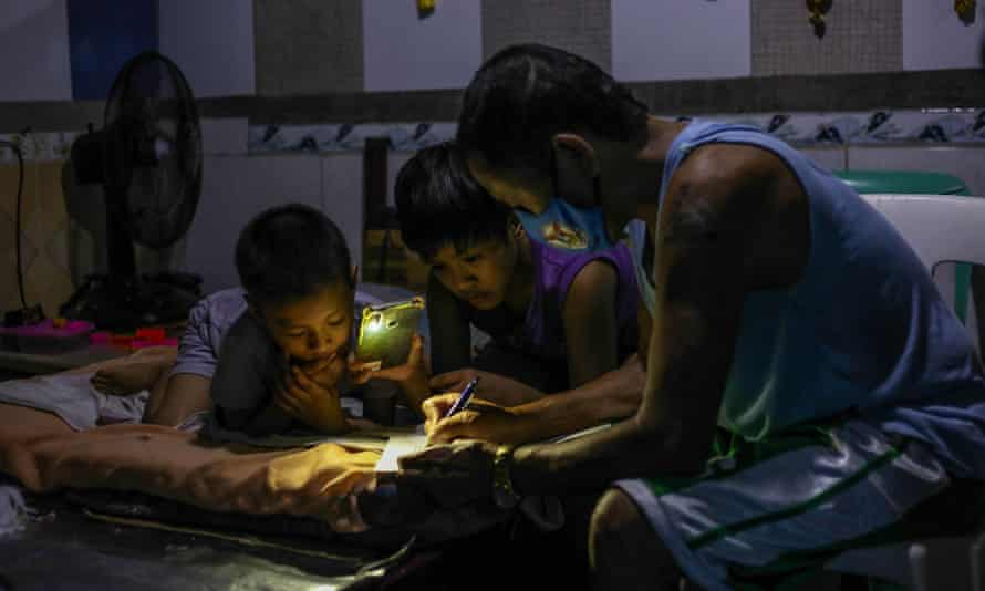 Petronilo Pacayra signs school documents with his children aged nine and 10, in Quezon City.