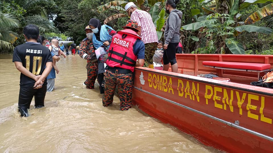 Fire and Rescue Department personnel assisting flood victims evacuated to the PPS at SJK (C) Chung Hua Trusan. ― Borneo Post pic