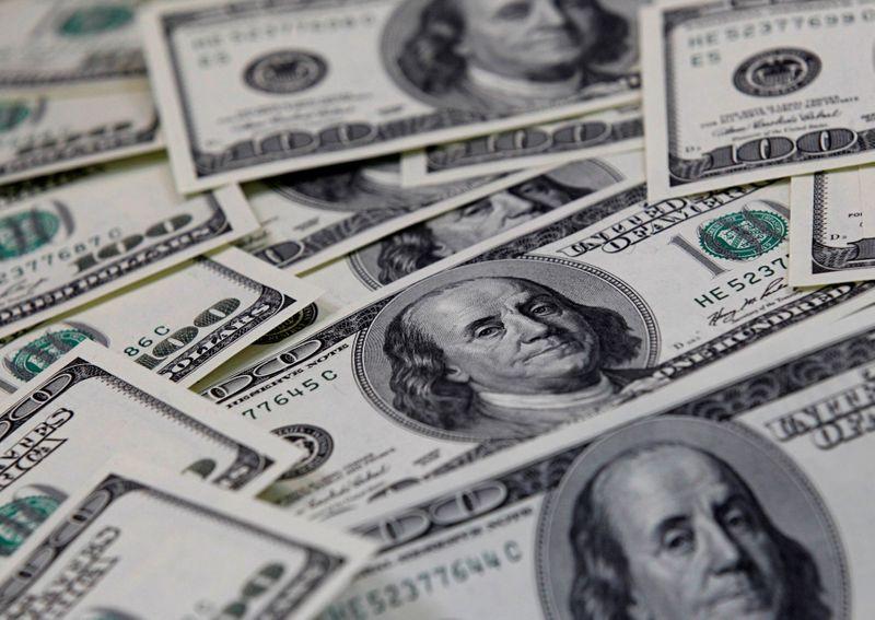 Dollar holds tight range as investors await U.S. inflation data