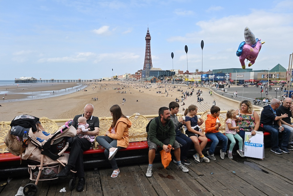 People relax on benches set out on the Central Pier in Blackpool, north west England on September 4, 2021. — AFP pic
