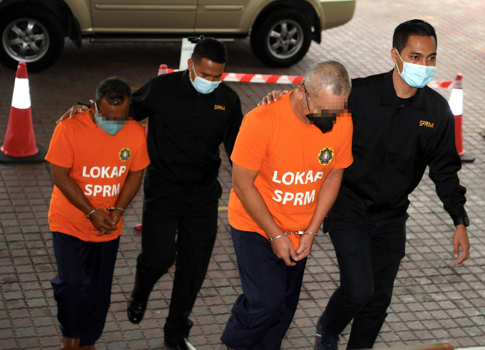 The two suspects, aged 54 and 51, arriving at the Sultan Salahuddin Abdul Aziz Court Complex at 10am accompanied by MACC officers, September 10, 2021. — Bernama pic
