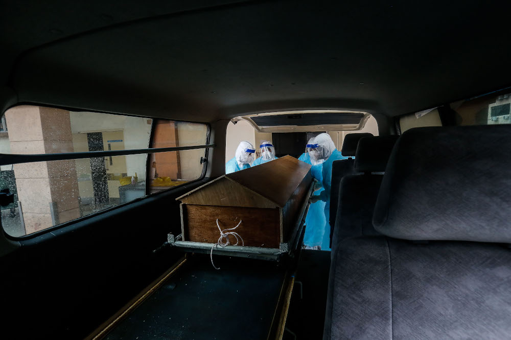 Forensics personnel prepare to transport the body of a recently deceased Covid-19 patient to a burial site from the Penang General Hospital August 24, 2021. — Picture by Sayuti Zainudin