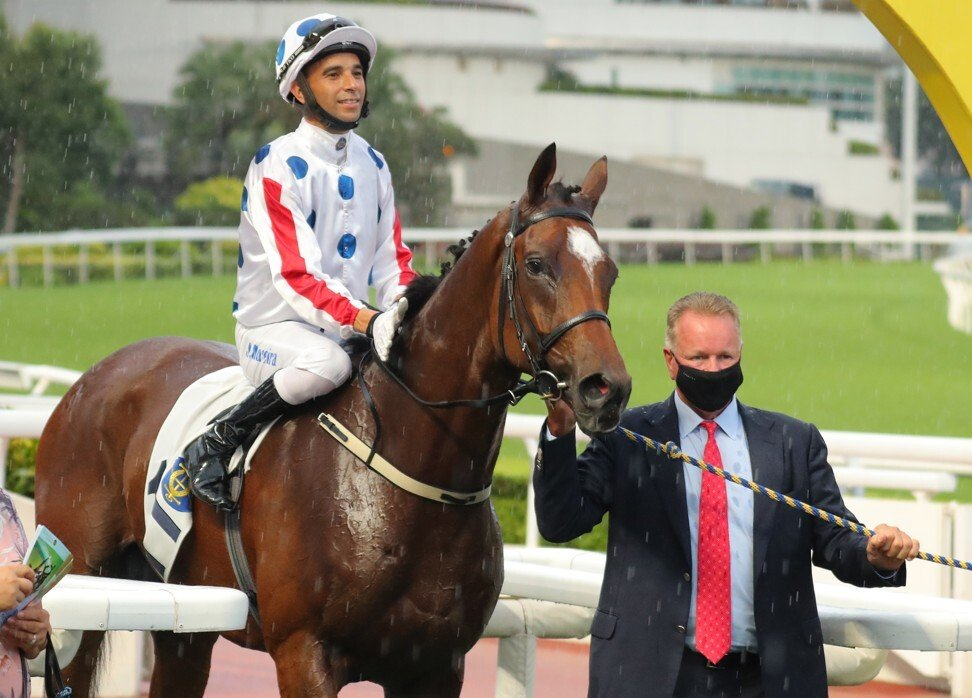 Jockey Joao Moreira and trainer Tony Millard celebrate C P Brave's victory.