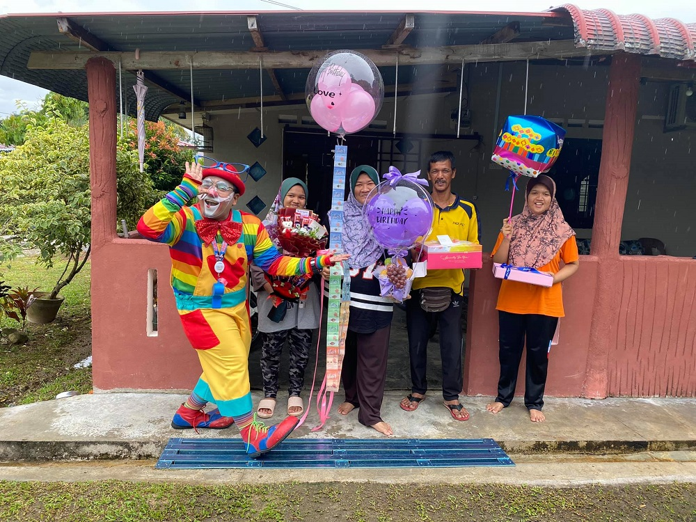 Shaharul (left) brought cheer to a family by delivering a birthday cake and entertaining the family. ― Picture via Facebook/ShaharulHisamBaharuddin