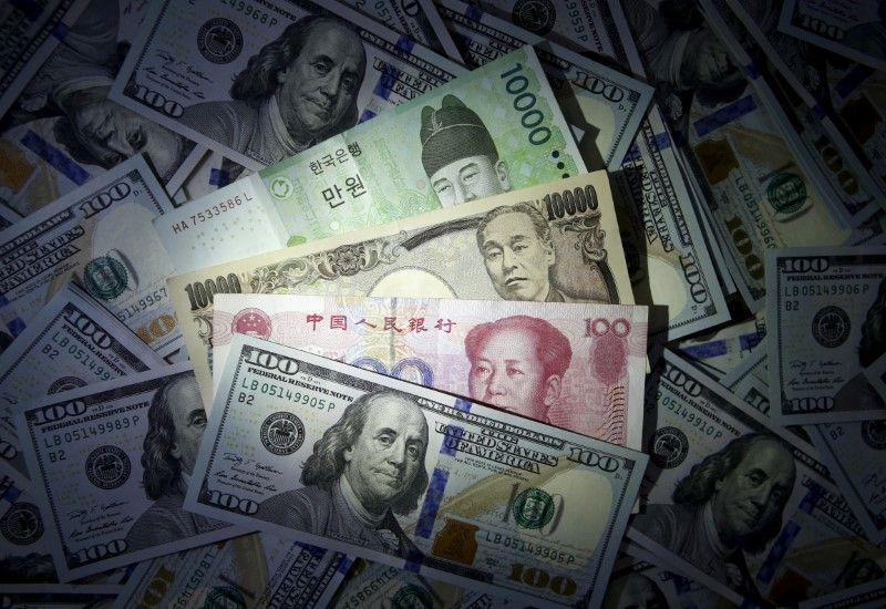 South Korean won, Chinese yuan and Japanese yen notes are seen on US 100 dollar notes in this file photo illustration shot April 15, 2017. ― Reuters pic