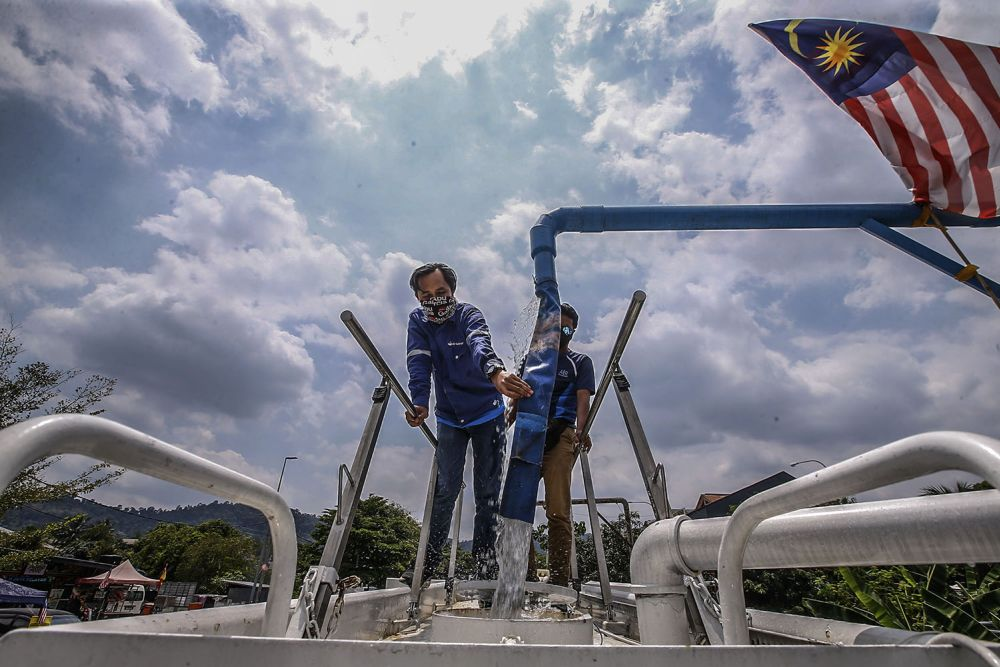 Air Selangor staff fill a water tanker amid water supply disruption in 998 areas in the Klang Valley on October 13, 2021. — Picture by Hari Anggara