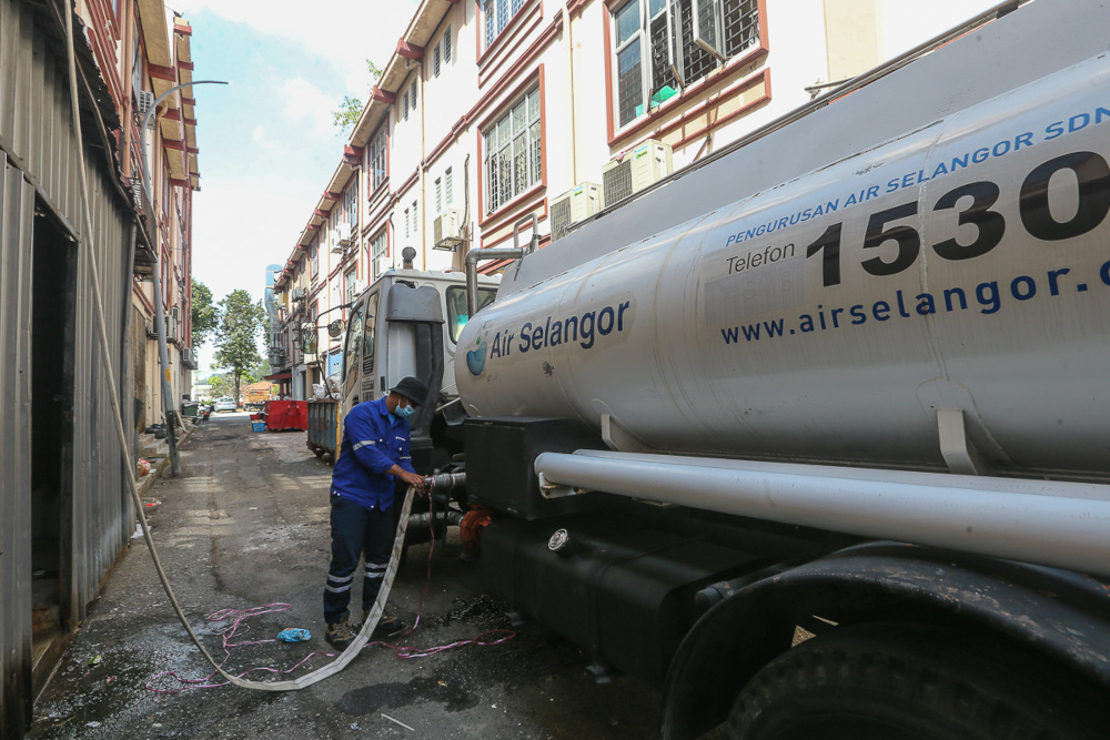 Air Selangor personnel distribute water to Pusat Dialisis Mukmin at Sri Andalas during water supply disruption in Klang, October 13, 2021. — Picture by Yusof Mat Isa