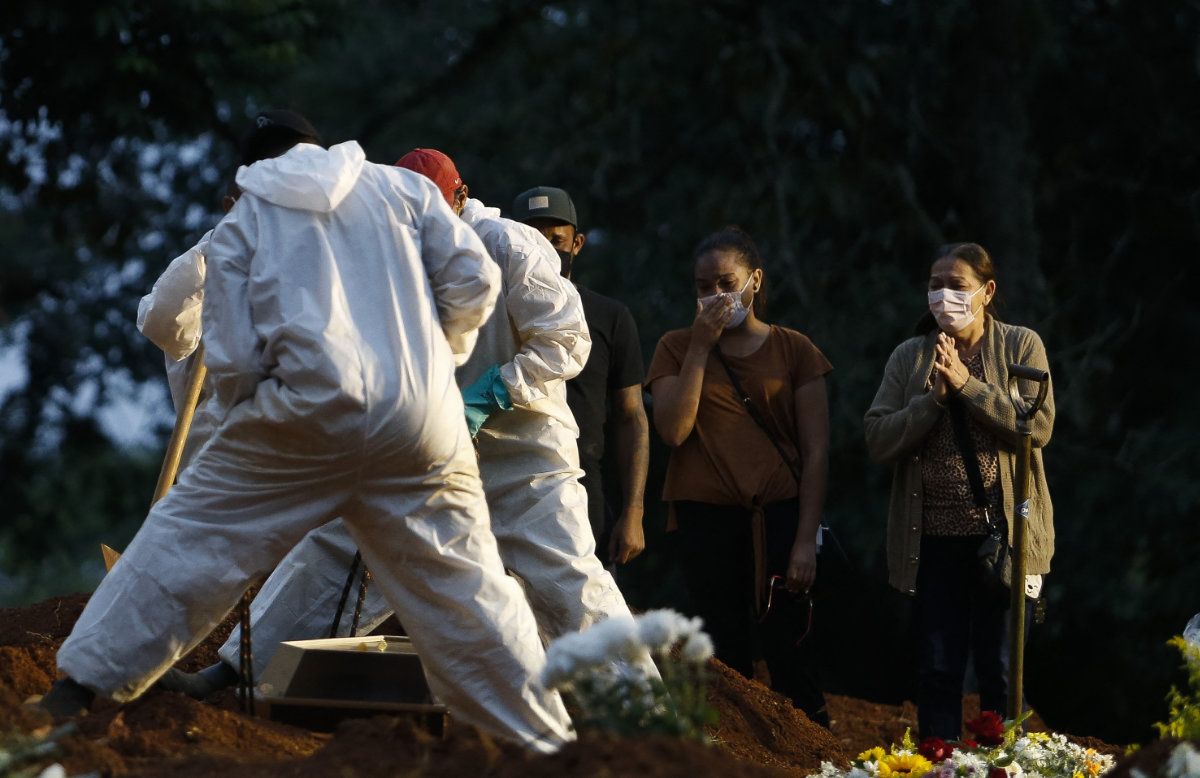 In this file photo taken on April 17, 2021 people mourn as a COVID-19 victim is buried by cemetery workers at the Vila Formosa cemetery in Sao Paulo, Brazil. (AFP)