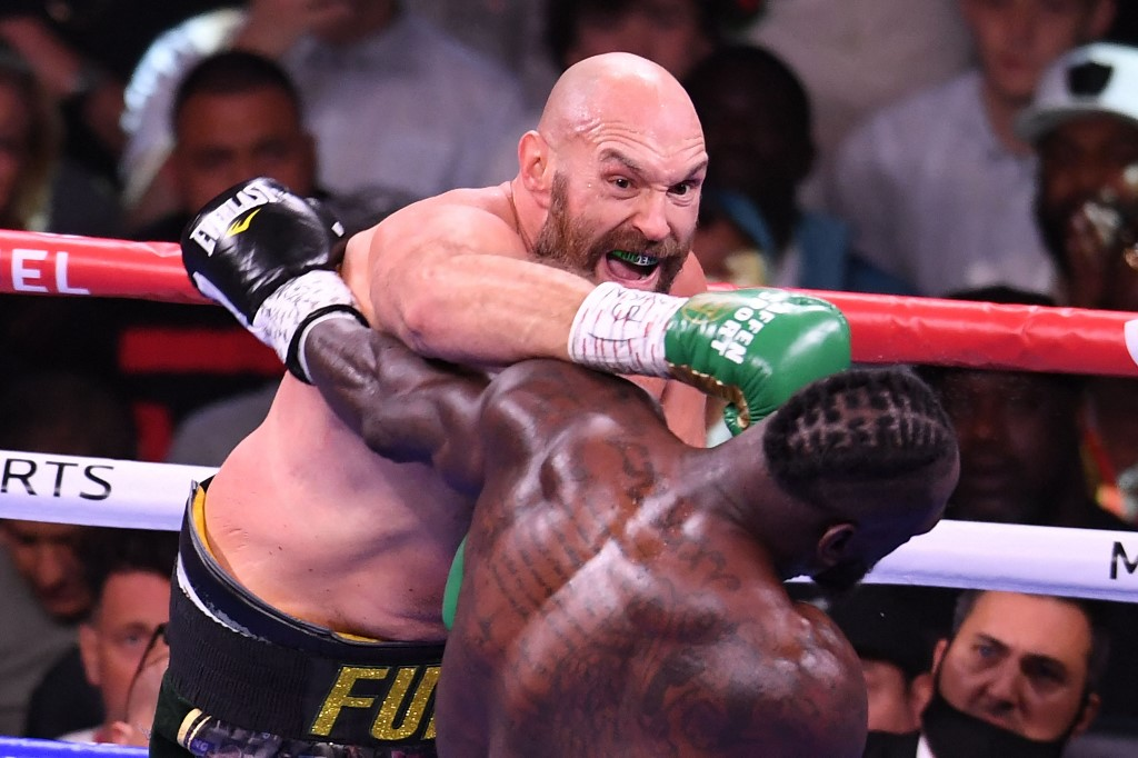 WBC heavyweight champion Tyson Fury of Great Britain (left) lands a punch on US challenger Deontay Wilder (right) in the third round fight for the WBC/Lineal Heavyweight title at the T-Mobile Arena in Las Vegas, Nevada, October 9, 2021. — AFP pic