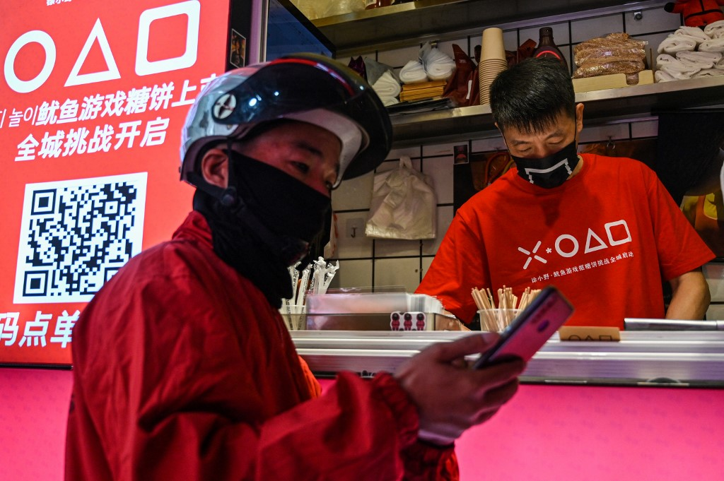 This photo taken on October 12, 2021 shows a delivery worker waiting next to a small shop for dalgonas, a crisp sugar candy featured in the Netflix series Squid Game, in Shanghai.