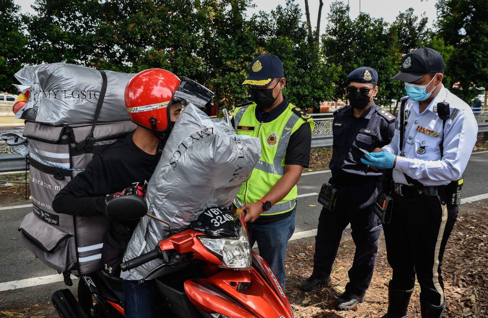 Selangor JPJ director Nazli Md Taib inspects a delivery rider during Ops Merah in Seri Setia, October 12, 2021. — Bernama pic