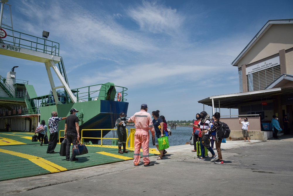 Travellers board the ro-ro ferry departing for Menumbok, Sabah at the main exit and entry gate at the Labuan International Ferry Terminal, October 13, 2021. — Bernama pic