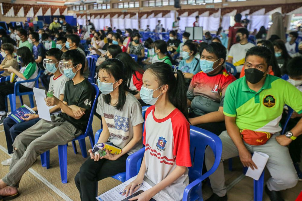 Students wait to receive their Covid-19 jab at SMA Izzuddin Shah in Ipoh October 5, 2021. — Picture by Farhan Najib