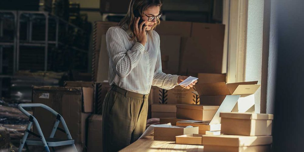 female-business-owner-talks-to-a-customer-on-the-phone-whilst-packing