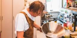 kok vult kommetje met frietjes in keuken van restaurant
