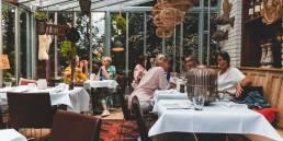 lachende mensen in de veranda van het restaurant aan tafel