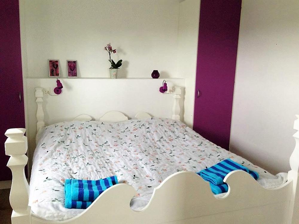 Ferielejlighedens soveværelse med dobbeltseng og skabe.